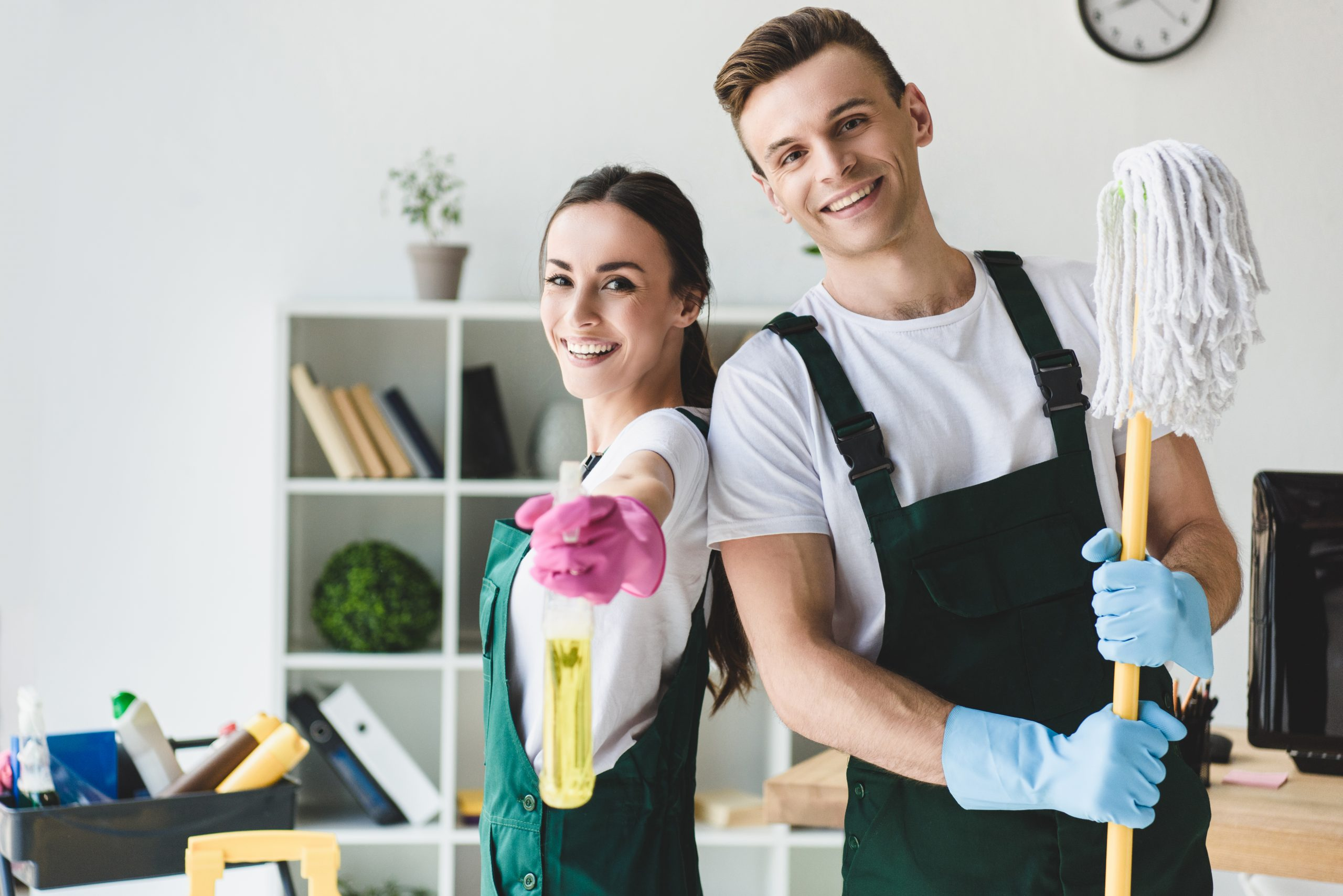happy young cleaners with mop and spray bottle smiling at camera while cleaning office
