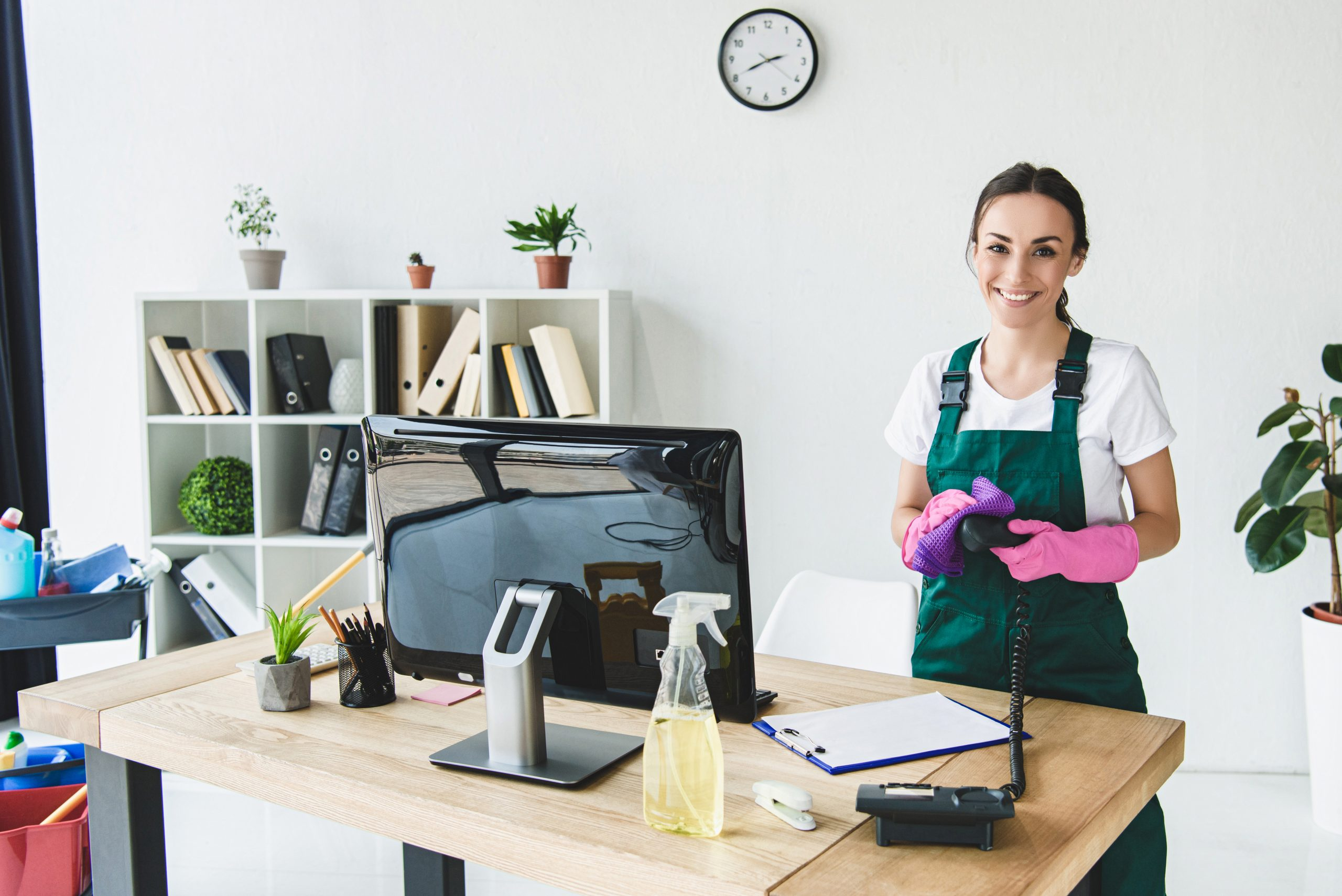 beautiful young professional cleaner smiling at camera while cleaning modern office