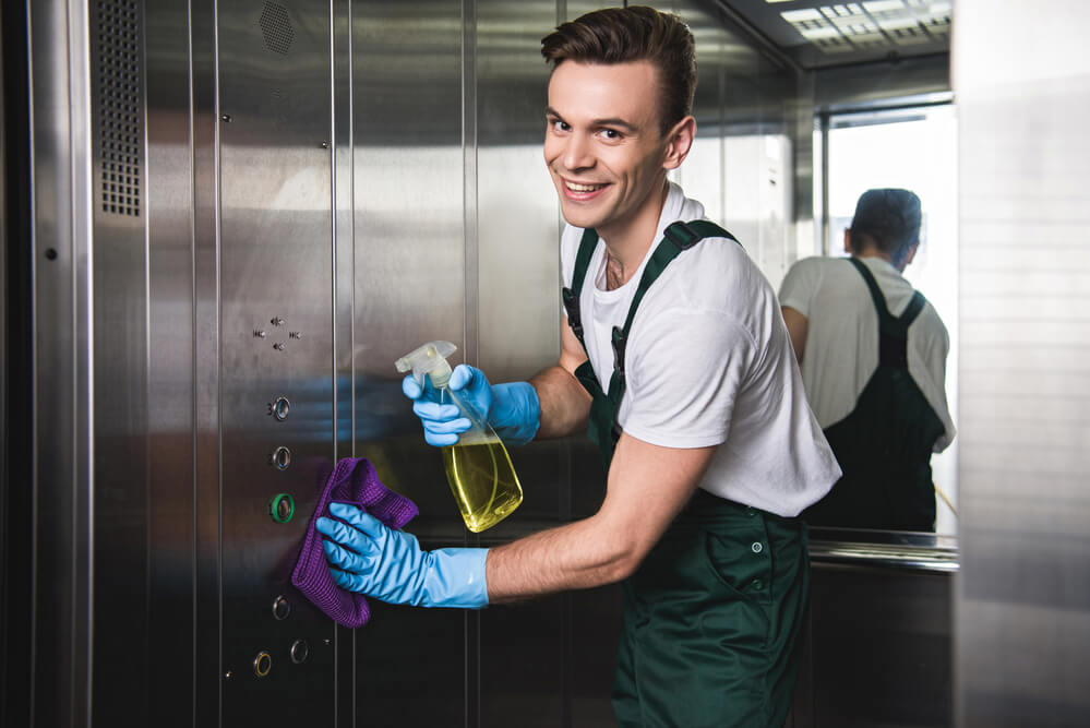 Commercial cleaner wiping down buttons in elevator